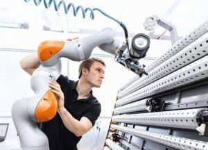 A worker guiding a collaborative robot.