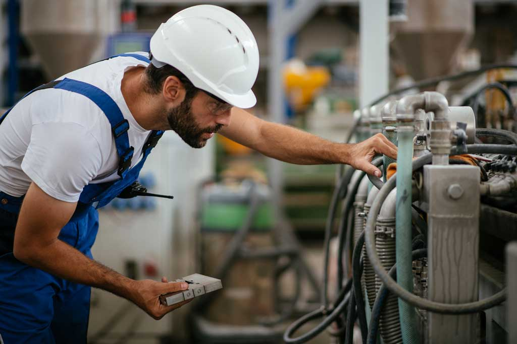hydraulic fluid selection: worker looking at machinery with fluid pipes
