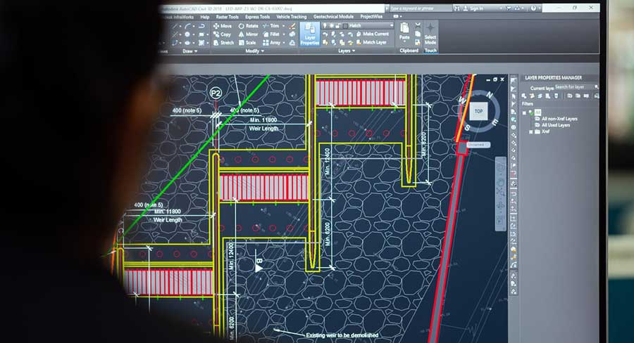 autocad: a man sitting in front of the screen with AutoCAD software running